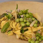 piatto di tagliatelle paglia e fieno con cipollotti caramellati, piselli freschi e menta