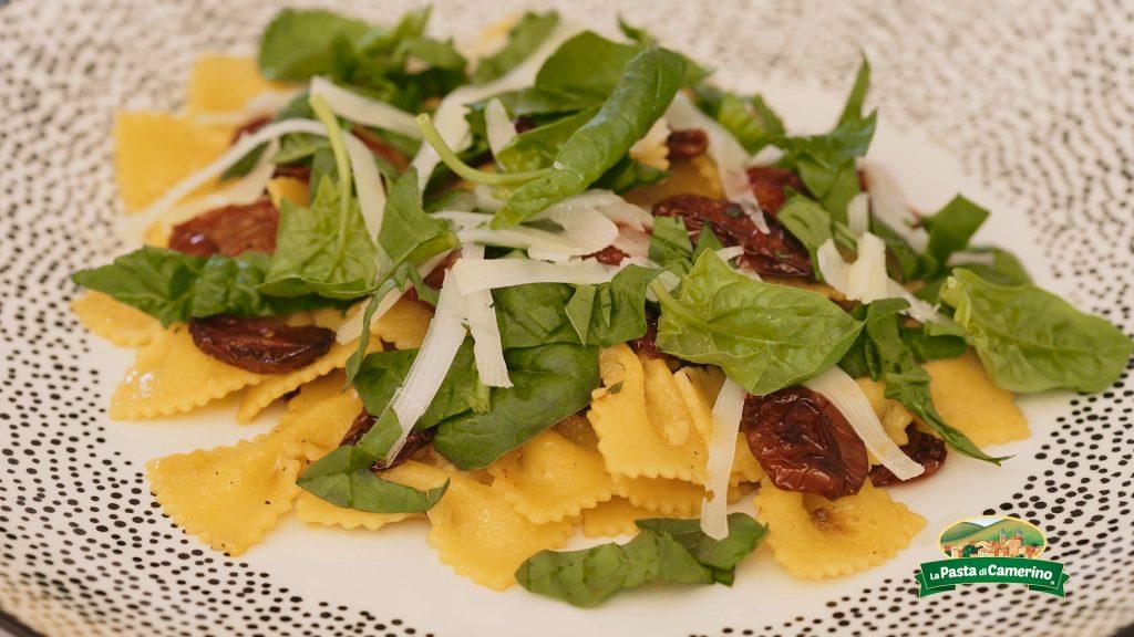 piatto di farfalle all'uovo con spinaci freschi, pomodorini confit e scaglie di pecorino