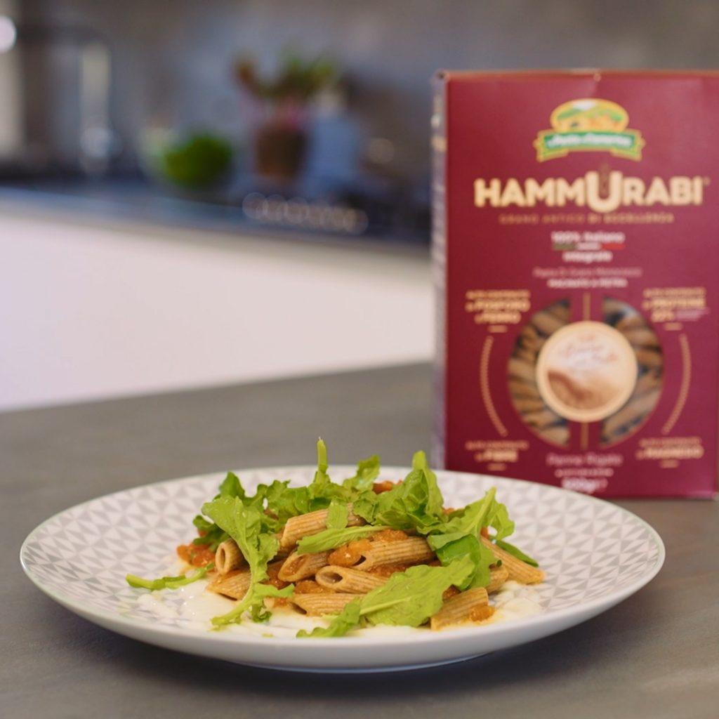 confezione e piatto di penne Hammurabi con crema all'aglio, polpa di pomodoro e insalata di rucola fresca